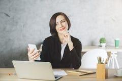 Empresaria sonriente hermosa que usa smartphone en el lugar de trabajo imagen de archivo