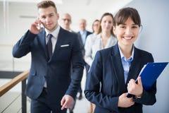 Empresaria sonriente Holding Clipboard While que camina con el equipo Foto de archivo libre de regalías