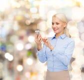 Empresaria sonriente joven con smartphone Imagenes de archivo