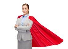 Empresaria sonriente joven en cabo rojo del super héroe fotos de archivo
