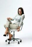 Empresaria sonriente joven que se sienta en la silla de la oficina fotografía de archivo