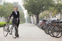 Empresaria sonriente joven que sostiene una bicicleta en la acera, Pekín Imagenes de archivo
