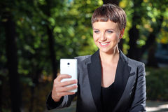 Empresaria sonriente joven que toma la foto con su teléfono outdoor Fotos de archivo