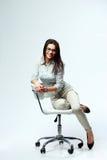 Empresaria sonriente joven siiting en la silla de la oficina imagen de archivo