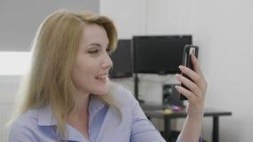 Empresaria sonriente magnífica que hace la llamada video usando smartphone en la oficina que dice hola al webcam - metrajes