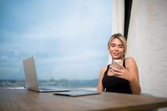 Empresaria sonriente que charla en línea en el teléfono móvil después de trabajo sobre el red-libro en oficina fotografía de archivo libre de regalías