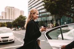 Empresaria sonriente que consigue en un taxi imagen de archivo libre de regalías