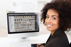 Empresaria sonriente que corrige las fotografías imagenes de archivo