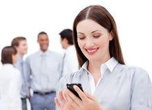 Empresaria sonriente que envía un texto Imágenes de archivo libres de regalías