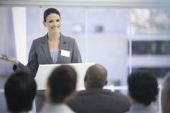 Empresaria sonriente que gesticula mientras que sus colegas la miran Foto de archivo libre de regalías