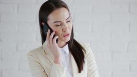Empresaria sonriente que habla en el teléfono metrajes