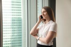 Empresaria sonriente que habla en el teléfono en la oficina, haciendo answeri Imágenes de archivo libres de regalías