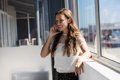 Empresaria sonriente que habla en el teléfono mientras que hace una pausa la ventana Imagen de archivo