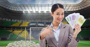 Empresaria sonriente que muestra el dinero en el estadio que representa la corrupción Imagenes de archivo