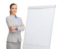 Empresaria sonriente que se coloca al lado de flipboard fotografía de archivo
