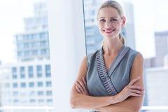 Empresaria sonriente que se coloca en la oficina Imagen de archivo