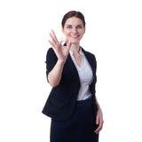 Empresaria sonriente que se coloca sobre fondo aislado blanco Foto de archivo libre de regalías