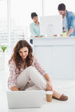Empresaria sonriente que se sienta en el piso usando el ordenador portátil Foto de archivo libre de regalías
