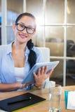 Empresaria sonriente que se sienta en su escritorio y que trabaja con la tableta Fotos de archivo libres de regalías