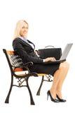 Empresaria sonriente que se sienta en un banco y que trabaja en un ordenador portátil Fotos de archivo libres de regalías