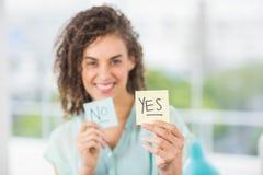 Empresaria sonriente que se sostiene sí y ningunos palillos Fotografía de archivo