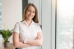 Empresaria sonriente que siente optimista en la oficina foto de archivo libre de regalías