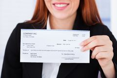 Empresaria sonriente que sostiene el cheque Imagenes de archivo