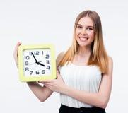 Empresaria sonriente que sostiene el reloj grande Fotos de archivo