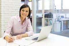 Empresaria sonriente que trabaja en la oficina, mirando la cámara Imagenes de archivo