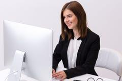 Empresaria sonriente que trabaja en la PC Imagenes de archivo