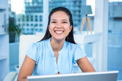 Empresaria sonriente que trabaja en su escritorio Foto de archivo libre de regalías