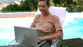 Empresaria sonriente que usa el poolside del ordenador portátil almacen de video