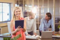 Empresaria sonriente que usa la PC digital con el trabajo masculino de los colegas Foto de archivo libre de regalías