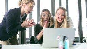Empresaria sonriente tres con el ordenador portátil, alto-fiving hermosos y animar almacen de video