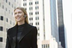 Empresaria sonriente Using Wireless Headset contra edificios Fotografía de archivo libre de regalías