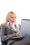 Empresaria sorprendente con la computadora portátil en silla imagen de archivo