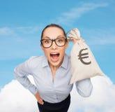 Empresaria sorprendente que sostiene el bolso del dinero con euro Foto de archivo libre de regalías
