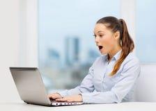 Empresaria sorprendida con el ordenador portátil Foto de archivo