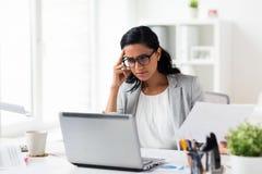 Empresaria subrayada con el ordenador portátil en la oficina Fotos de archivo libres de regalías