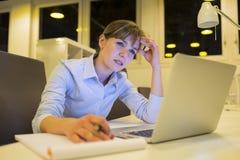 Empresaria subrayada que trabaja tarde en oficina Imagen de archivo