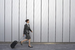 Empresaria With Suitcase Walking al aire libre Foto de archivo libre de regalías