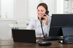 Empresaria Talking On Phone mientras que trabaja en el ordenador portátil Imagen de archivo libre de regalías