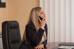 Empresaria Talking On Telephone en oficina Fotografía de archivo libre de regalías