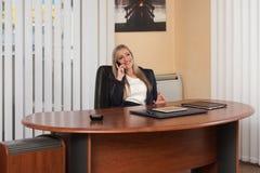 Empresaria Talking On Telephone en oficina Fotos de archivo libres de regalías