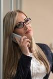 Empresaria Talking On Telephone en oficina Imagenes de archivo