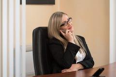 Empresaria Talking On Telephone en oficina Fotografía de archivo