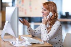 Empresaria Talking On Telephone en oficina Foto de archivo