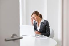 Empresaria tensionada que trabaja en oficina Foto de archivo