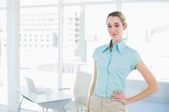 Empresaria tranquila atractiva que presenta en su oficina con la mano en cadera Foto de archivo libre de regalías