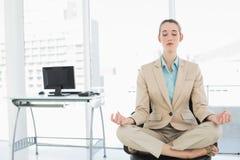 Empresaria tranquila concentrada que se sienta en la posición de loto respecto a su silla de eslabón giratorio Imagen de archivo libre de regalías